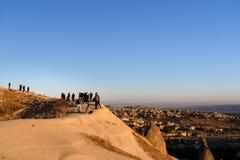 Aufpassender Sonnenaufgang der Leute mit Ballonen auf Klippe in Goreme Cappadocia Die Türkei Lizenzfreie Stockfotografie