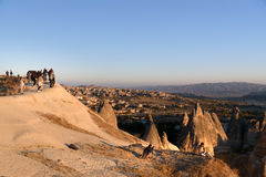 Aufpassender Sonnenaufgang der Leute mit Ballonen auf Klippe in Goreme Cappadocia Die Türkei Stockfotografie
