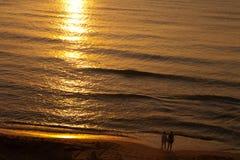 Aufpassender Sonnenaufgang von zwei Patience Leuten in Meer stockfoto