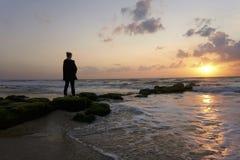 Aufpassender Sonnenuntergang der Frau am Strand stockfotografie