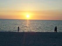 Aufpassender Sonnenuntergang der Leute auf dem Strand lizenzfreie stockbilder