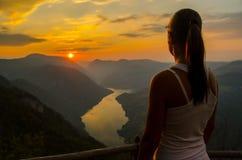 Aufpassender Sonnenuntergang des Mädchens von der Spitze des Berges Stockfoto