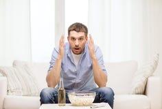 Aufpassender Sport des traurigen Mannes zu Hause Lizenzfreies Stockfoto