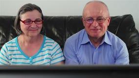 Aufpassendes Fernsehen der glücklichen älteren Paare stock video footage