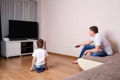 Aufpassendes Fernsehen des Vaters und des Sohns zusammen lizenzfreie stockfotos