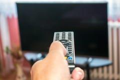 Aufpassendes Fernsehen und Anwendung der Fernbedienung stockfotos