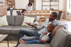 Aufpassendes Fernsehen Vater-And Sons Sit On Sofa In Lounge stockfoto