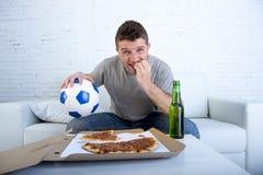 Aufpassendes Fußballspiel des jungen Mannes auf beißendem Fingernagel des Fernsehnervösen und aufgeregten Leidendruckes auf Sofa Lizenzfreies Stockbild
