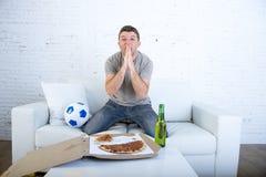 Aufpassendes Fußballspiel des jungen Mannes auf betendem Gott des Fernsehnervösen und aufgeregten Leidendruckes für Ziel Lizenzfreies Stockbild