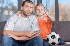 Aufpassendes Fußballspiel des Vaters und des Sohns lizenzfreies stockbild