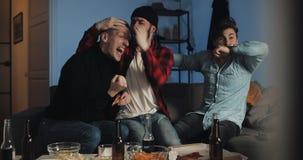 Aufpassendes Fu?ballspiel von drei Freunden im Fernsehen zu Hause, bestem Fu?ballteam zujubelnd gef?hl Die Fans der M?nner feiern stock video footage
