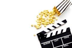 Aufpassendes Konzept des Filmes Clapperboard und Popcorn auf weißem Draufsicht-Kopienraum des Hintergrundes lizenzfreie stockfotografie