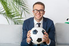 Aufpassendes Match des jungen Geschäftsmannsportfreunds, welches das Kameralächeln schaut stockfotografie