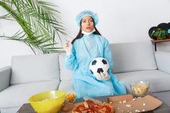 Aufpassendes Match des Sportfreunds der jungen Frau verwechselt mit Spiel lizenzfreie stockfotografie