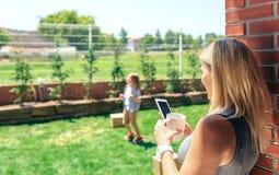 Aufpassendes Mobile der Mutter, während Sohn spielt stockfotografie