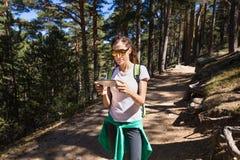 Aufpassendes Mobile der Wandererfrau auf einem Waldweg Stockbilder