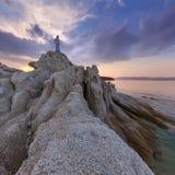 Aufpassendes Sonnenunterganghoch des einzelnen Mädchens oben auf Klippe durch Meer Stockfoto