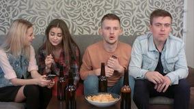 Aufpassendes Sportspiel der Jungen im Fernsehen zu Hause, Alkohol trinkend, während Mädchen, die Internet auf Smartphone surfen Lizenzfreies Stockfoto