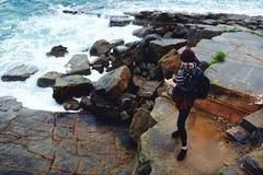 Aufpassendes Video des jungen stilvollen Hippie-Mädchens am Zelltelefon während des Restes nahe Ozean Stockfotos