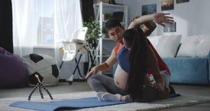 Aufpassendes Video des Mannes und der schwangeren Frau während des Trainings