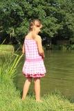Aufpassendes Wasser des kleinen Mädchens im Teich Stockfotografie