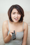 Aufregende Hand der jungen Frau, welche die Fernbedienung fernsieht hält Lizenzfreies Stockfoto