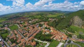 Aufregende Landschaft des italienischen Dorfs liegend nahe grasartigem Hügel unter blauem Himmel stock footage