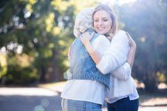 Aufrichtige junge Frau, die draußen alte Mutter umarmt Stockbilder