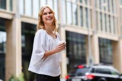 Aufrichtige lachende junge blonde Frau gegen städtischen Stadthintergrund Stockbild