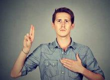 Aufrichtiger Mann, der mit der Hand auf Herzen schwört Stockfoto