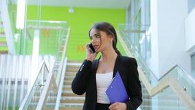 aufruf Geschäftsfrau, die am Handy in der Büromitte spricht stock video footage