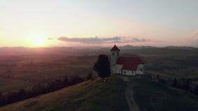 Aufschlussreiches Trieb einer katholischen Kirche auf einem Hügel mit einer schönen Ansicht zum Dorf in der Sommerzeit im Sonnenu stock video