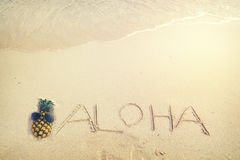 Aufschrift Aloha geschrieben auf den sandigen Strand mit Meereswogen Lizenzfreies Stockbild