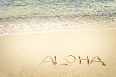 Aufschrift Aloha geschrieben auf den sandigen Strand mit Meereswogen Stockbild