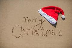 Aufschrift auf dem nassen Sand und der Kappe von Santa Claus Lizenzfreies Stockbild