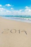 Aufschrift 2014 auf Meersandstrand mit der Sonne strahlt aus Stockfoto