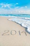 Aufschrift 2014 auf Meersandstrand mit der Sonne strahlt aus Lizenzfreies Stockfoto