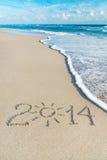 Aufschrift 2014 auf Meersandstrand mit der Sonne strahlt aus Stockbild