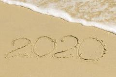 Aufschrift 2020 auf Sand mit Gischt Lizenzfreies Stockbild