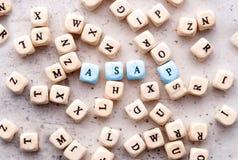 Aufschrift SO BALD WIE MÖGLICH sobald posisioble Abkürzung in den hölzernen Buchstaben auf einem hellen Hintergrund lizenzfreies stockbild