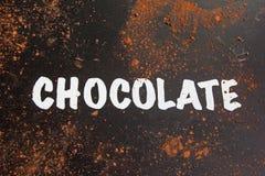 """Aufschrift """"chocolate† am dunklen Tisch mit Schokoladenpulver lizenzfreie stockfotografie"""