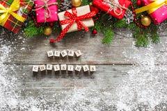 Aufschrift der frohen Weihnachten auf Holzklötzen Abstraktes Hintergrundmuster der weißen Sterne auf dunkelroter Auslegung Stockfoto