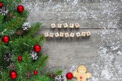Aufschrift der frohen Weihnachten mit Tannenzweigen, festlichen Dekorationen und Kiefernkegeln auf rustikalem Holztisch Stockfotografie
