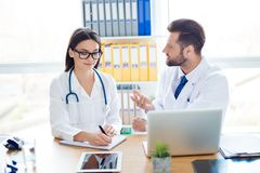 Aufschrift der roten Farbe gelegen über Text der weißen Farbe Zwei Medizinerarbeitskräfte in den weißen Mänteln sind Diskette stockbilder