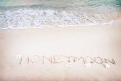 Aufschrift-Flitterwochen geschrieben auf den sandigen Strand mit Meereswogen Lizenzfreies Stockbild