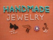 Aufschrift gemacht von den Perlen, vom handgemachten Schmuck, von den Möbeln und von den Werkzeugen Stockfotografie
