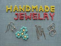 Aufschrift gemacht von den Perlen, vom handgemachten Schmuck, von den Möbeln und von den Werkzeugen Stockbilder