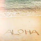 Aufschrift geschrieben auf den sandigen Strand mit Meereswogen Stockfotos