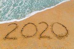 Aufschrift 2020 geschrieben auf sandigen Strand mit dem Wellennähern Lizenzfreie Stockfotos
