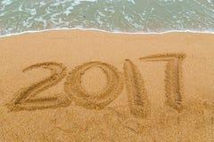 Aufschrift 2017 geschrieben auf sandigen Strand mit dem Wellennähern Stockfotografie
